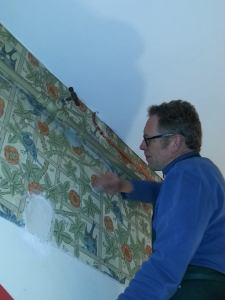 Our Wallpaper Conservator cleaning the Trellis wallpaper in the Dog Leg Corridor
